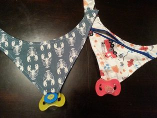 Natalie Higgs has pacifier holders in many different fabric designs! Find her December 7th!