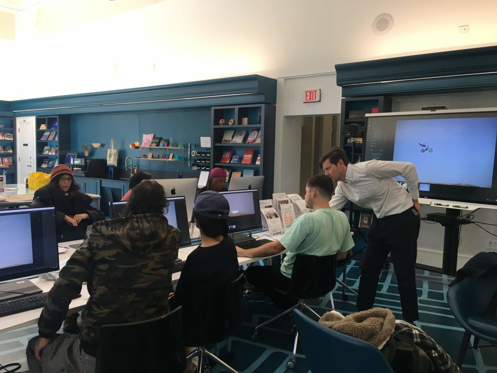 six individuals working on projects at computers