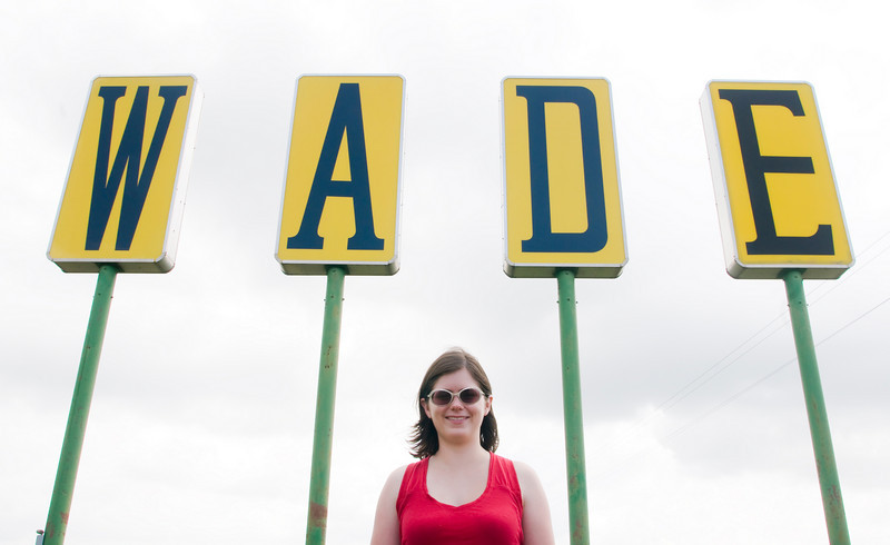 Lizzie Wade, under the W A D E Tractor sign outside of Clarksdale