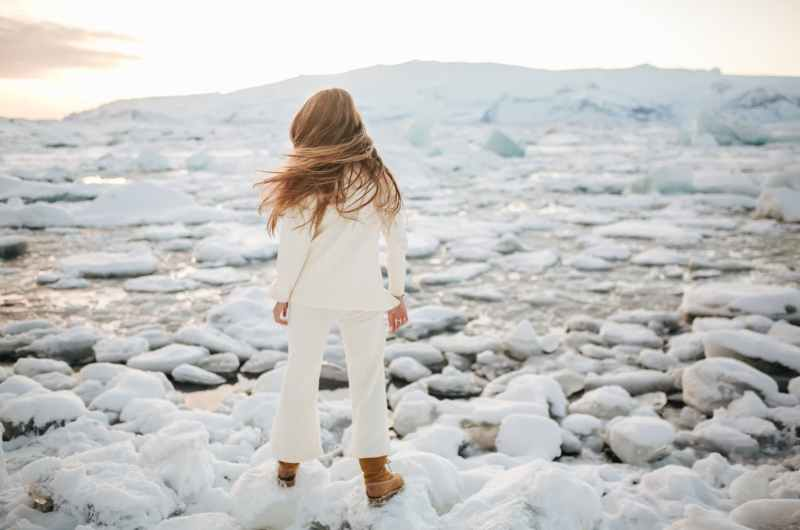 a woman standing on snow covered rocks near a frozen river