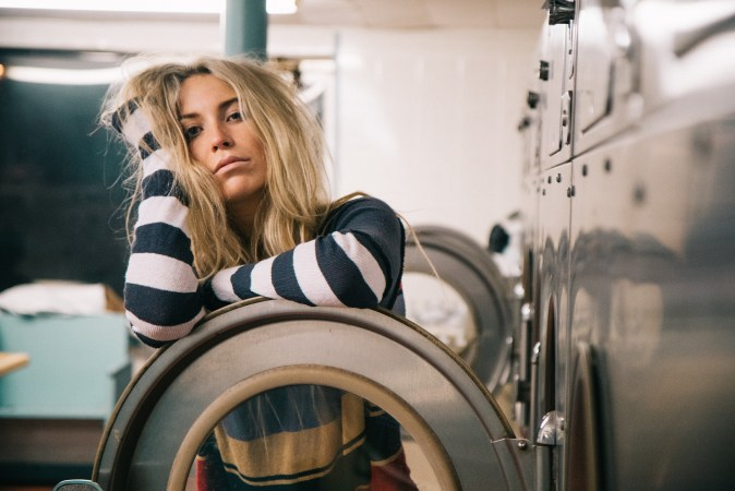Sad girl leaning on washing machine