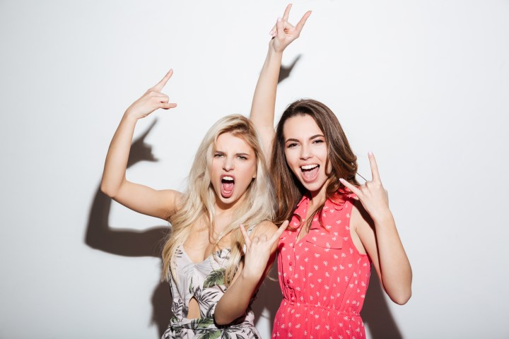 Two happy women doing peace signs