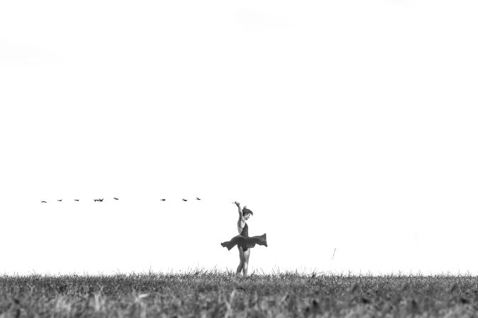 Black and white photo of lady with a kite in the wind