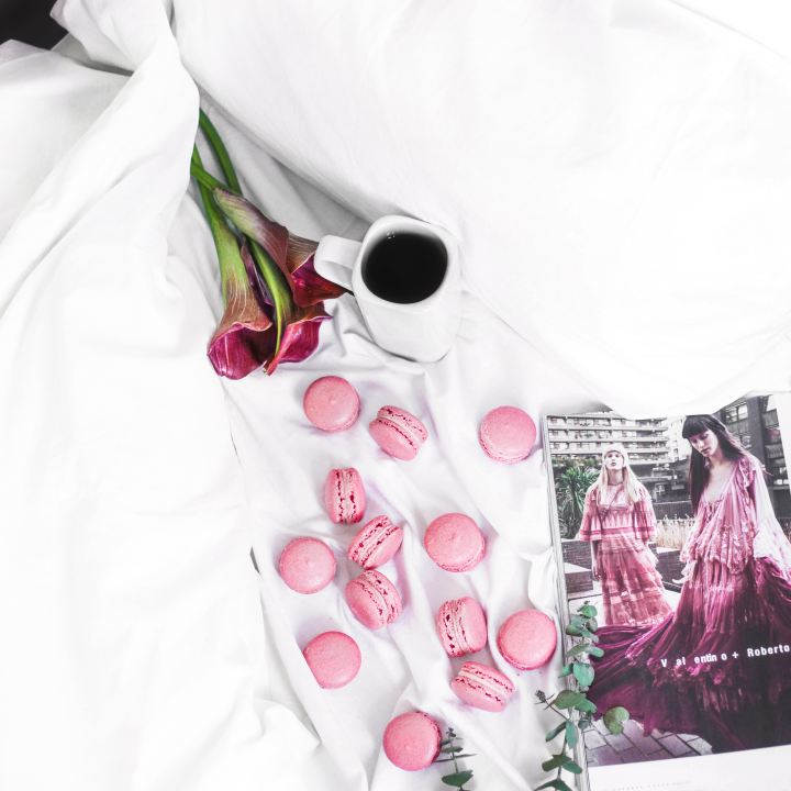 Picture of pink flowers and macarons with coffee and magazine on a bed