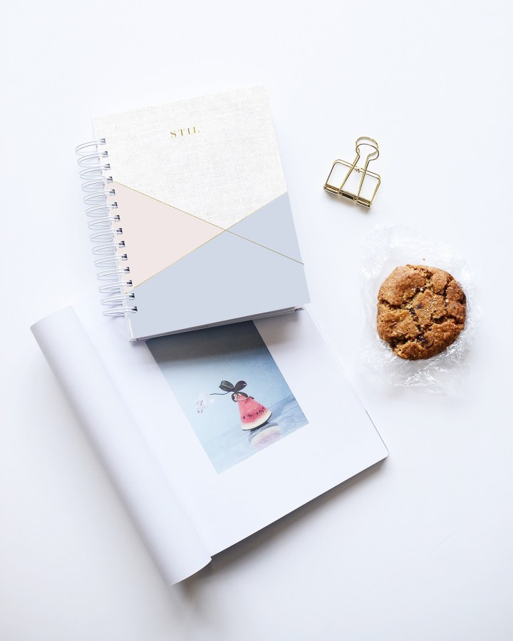 Picture of notebook, magazine, cookie and paperclip on table