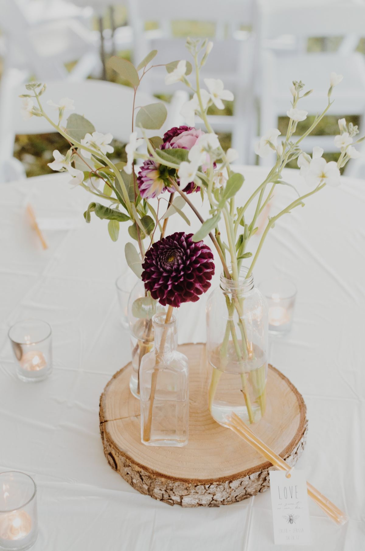 flowers on a table in small vases with candles