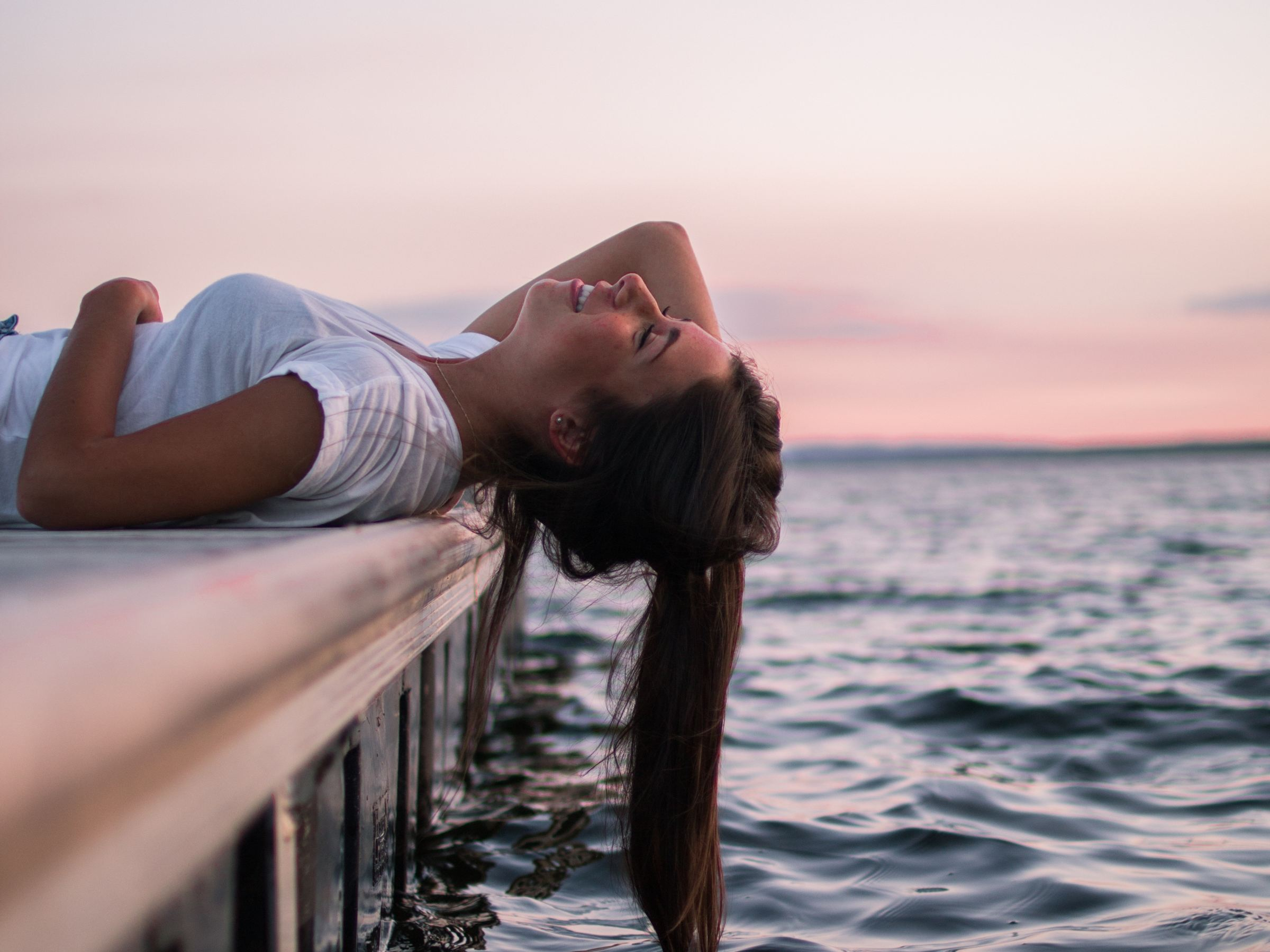 Photo of a lady lying on a pier with her hair in the water