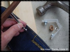 Applying the jeans button is the same technique. You can see the plastic gizmo is the same, but the attachments for it are larger. First: tap your cork screw/nail/brad awl a couple of times with your hammer to make a hole in your jeans where the button is to go.