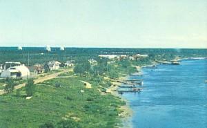 Moosonee c. 1962. Town and Moose River in foreground, radar base and domes in the background. Source: Moosonee Postcards, Paul Lantz website.