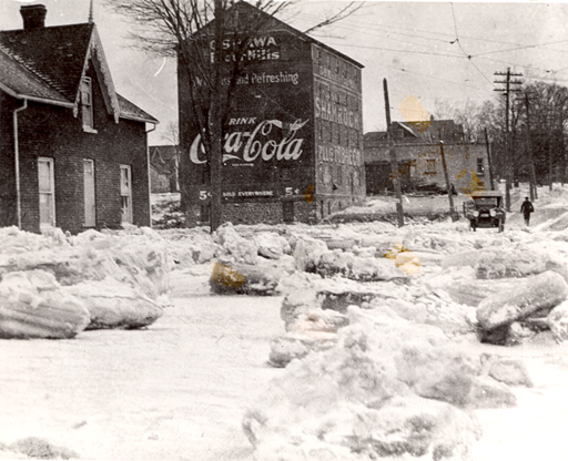 """This image looks east towards what was to become Oshawa's downtown, and shows the extent to which the realization of the  automobile landscape was temporally and physically removed from the cultural conception of this ideal. 'Spring Flood in the """"Hallows,""""' Thomas Bouckley Collection, Robert McLaughlin Gallery, 394 0355, 1922."""