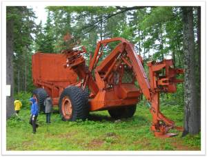 Environmental historians inspect a decommissioned, all-in-one mechanical harvester at the Central New Brunswick Woodsmen's Museum in Boiestown.