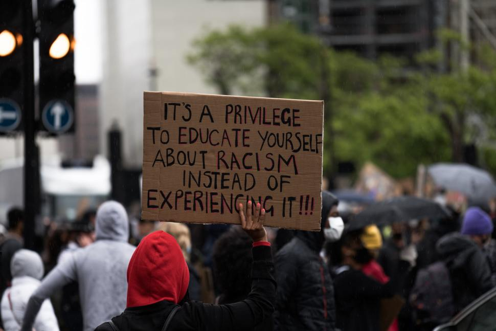 "At a racial justice protest a person of colour holds a cardboard sign that says ""It's a privilege to educate yourself about racism instead of experiencing it!!!"""