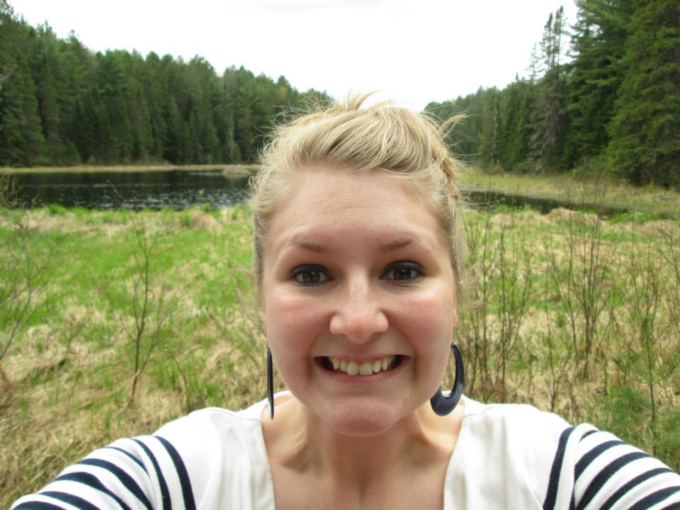Jessica DeWitt, a white, blond, woman, takes a selfie with a strained smile in front of a wetland made by beavers at Algonquin Provincial Park