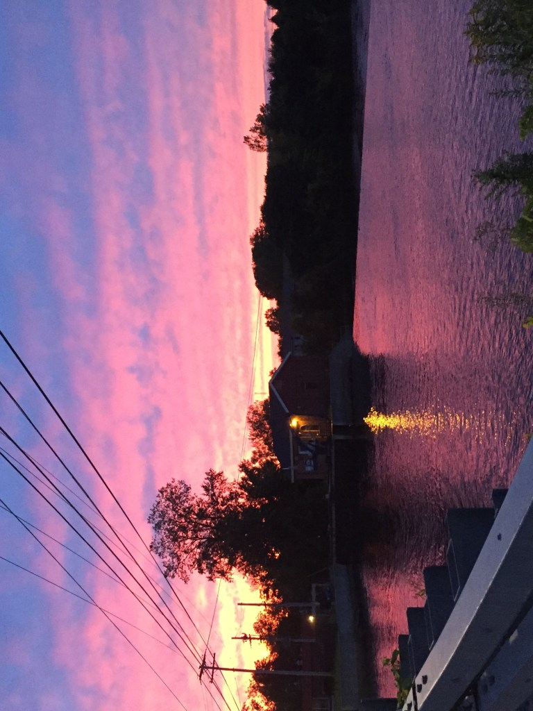 A blue, pink, and yellow sunset over a river. Telephone wires cross the upper third.