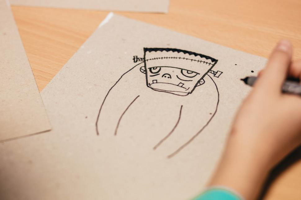 A hand drawing a simple image of Frankenstein's monster.