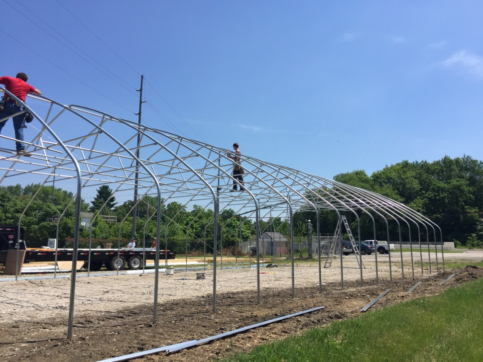 People constructing the metal frame shown in image 1, with blue skies and green trees in the background