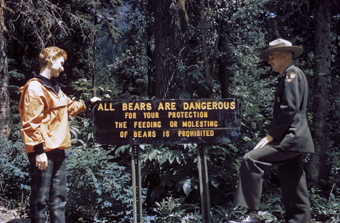 """A tourist and a park ranger stand in front of a sign that says """"All bears are Dangerous"""""""
