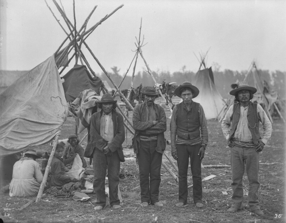 Four Swampy Cree men standing, in the background you can see an encampment with women and children