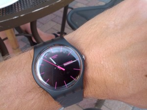 A black swatch watch on a wrist with pink time markings