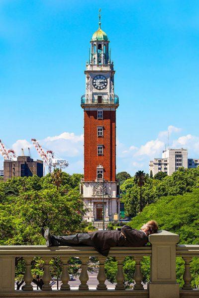 Un'uomo riposa di fronte alla Torre Monumentale di Buenos Aires