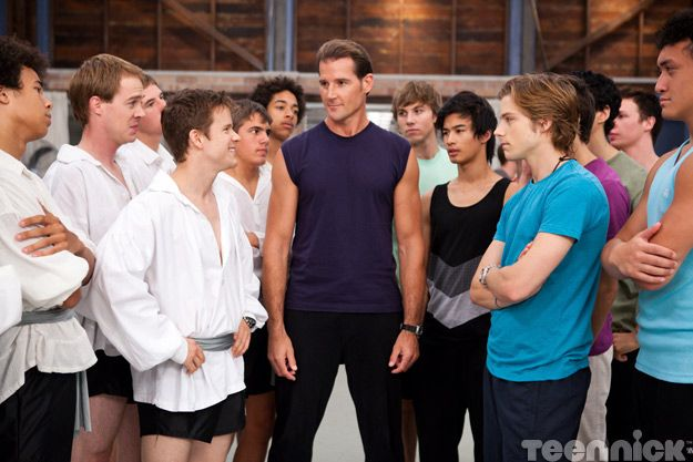 Half a dozen footballers (in ballet costumes) stand opposite the ballet students.  A male teacher stands in the middle.