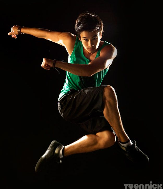 An athletic young Asian man captured mid-leap on a black background.