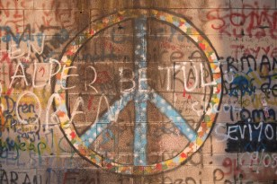 Peace symbol and graffiti spray-painted on wall