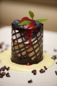 Cylindrical cheesecake in chocolate basket with blueberries
