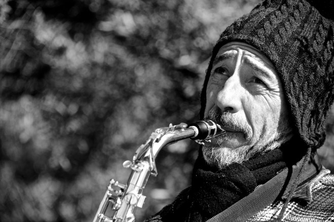 Mono close-up of bearded saxophonist in hat