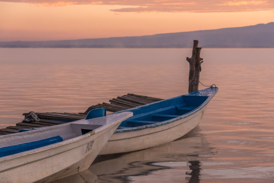 Two boats moored by jetty at dawn