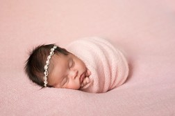 Newborn baby girl wrapped in pink in an adorable studio portrait by MN Newborn Photographer Nicki Joachim Photography of Owatonna Minnesota