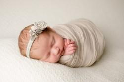 newborn baby girl wrapped in ivory in studio gorgeous portrait taken by MN Newborn Photographer Nicki Joachim Photography of Owatonna Minnesota