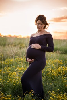 pregnant mama wearing a navy maternity gown standing in yellow flowers in a beautiful sunset portrait by MN Maternity Photographer Nicki Joachim Photography of Owatonna Minnesota