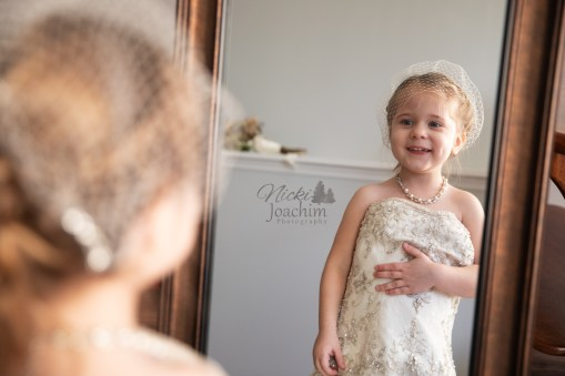 girl in mother's wedding dress looking at her reflection by MN Wedding Photographer Nicki Joachim Photography of Owatonna, Minnesota