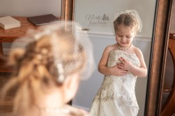 happy girl wearing mother's wedding dress in a styled lifestyle portrait by MN Wedding Photographer Nicki Joachim Photography of Owatonna, Minnesota