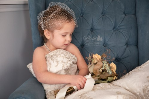 young girl sitting in her mother's wedding dress with bridal bouquet in a styled portrait by MN Wedding Photographer Nicki Joachim Photography of Owatonna, Minnesota