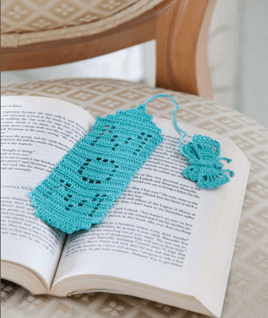 Crocheted red bookmark with the word mom on an open book on a wooden surface