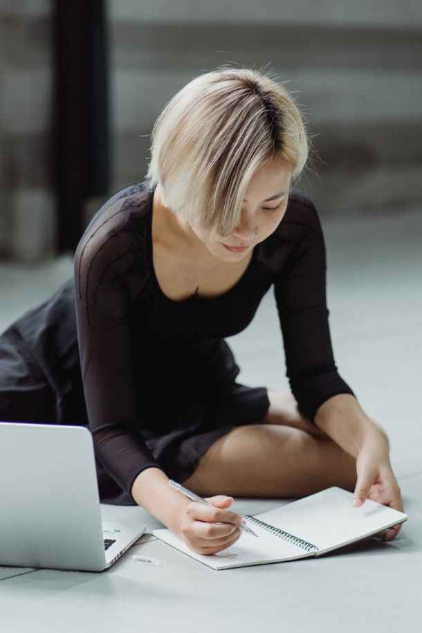 focused ethnic woman writing notes in notepad