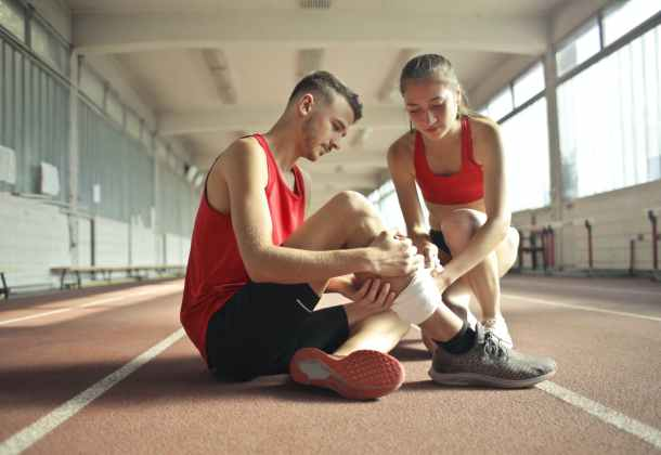 woman helping sportsman with injury during cardio training