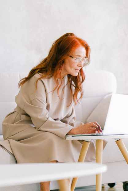 elderly woman with red hair typing on keyboard of laptop