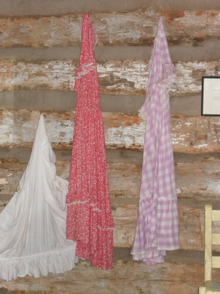 Pioneer dresses hang on nails in Frontier Village cabin