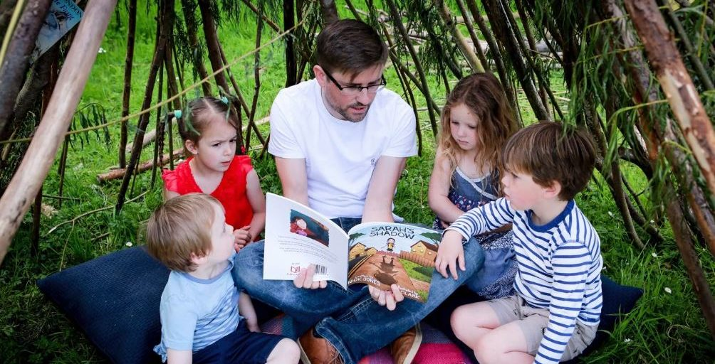 Photo of Nick jones reading to kids