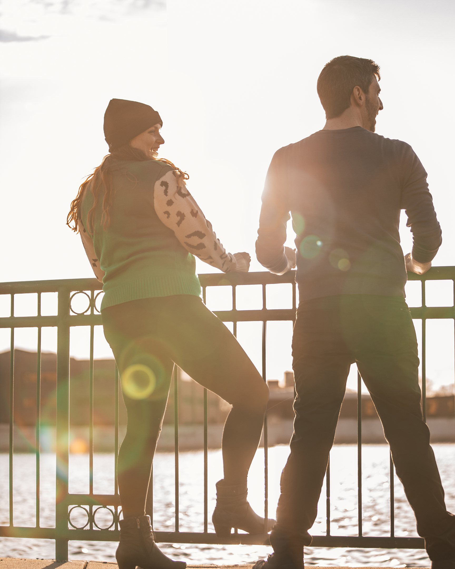 couple looking over railing onto grand rapids river with sun shinning thru