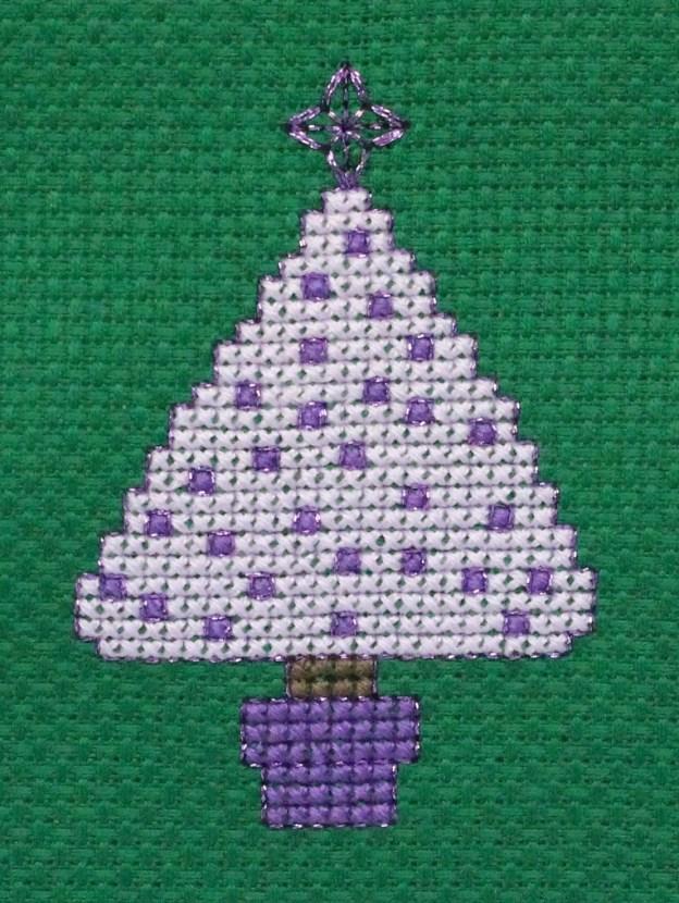 a lilac cross stitched Christmas tree on green aida fabric