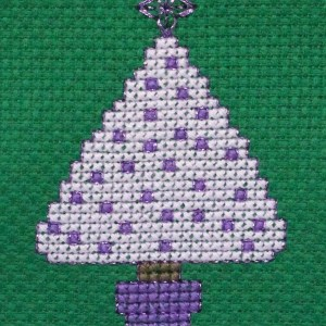 a lilac cross stitched Christmas tree on green aida fabric