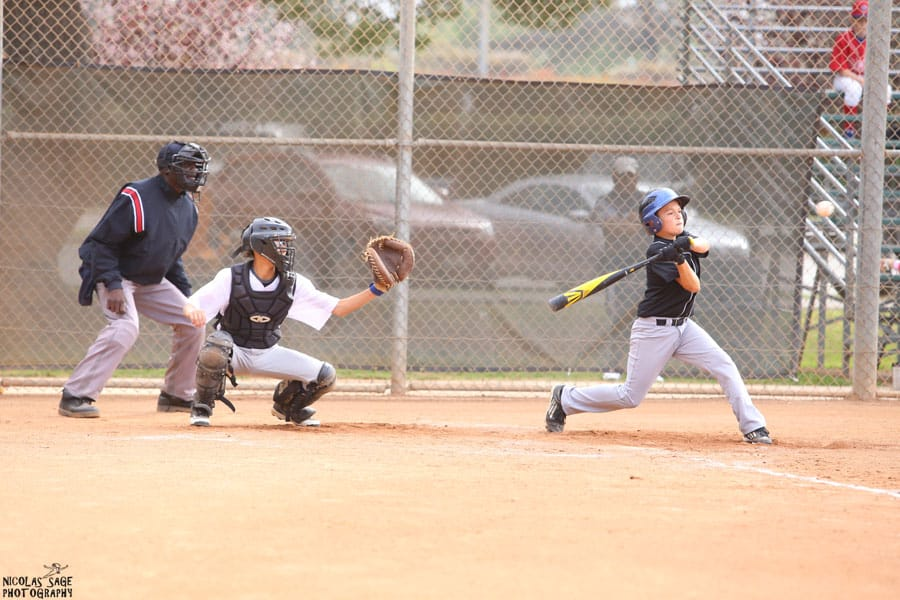 teenage boy hitting baseball with bat youth sports photography in los angeles