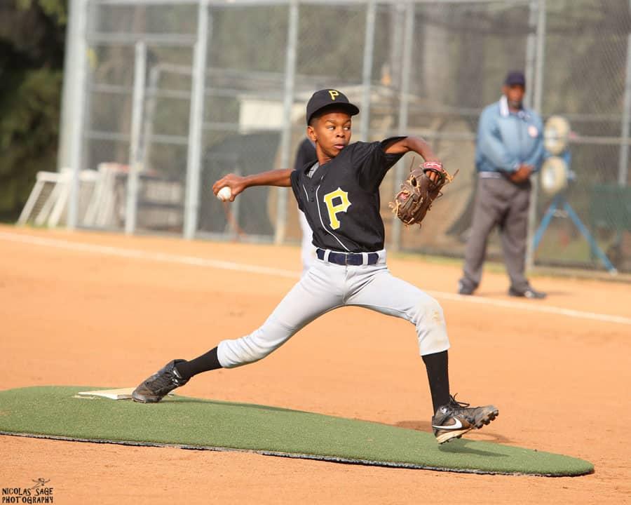 teenage boy throwing baseball in uniform