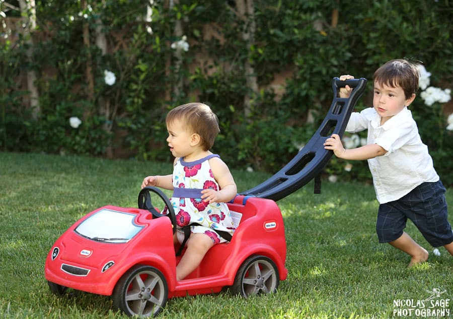 candid portrait of young siblings playing with toy car in Pacific Palisades