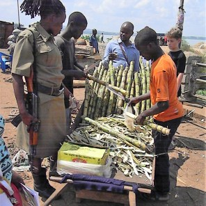 People selling sugar cane, and a guard with a gun