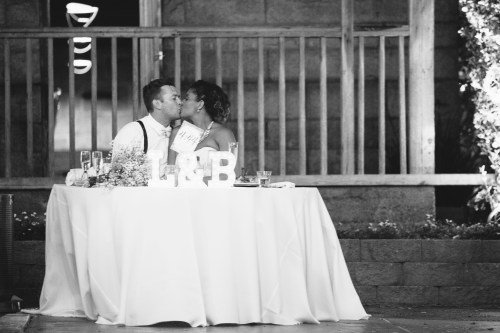 temecula creek inn weddings stonehouse reception head table bride and groom kissing